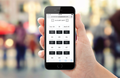 """alt=""""EscapeAssist's user-friendly escape room booking system calendar shown on hand held cell phone"""""""