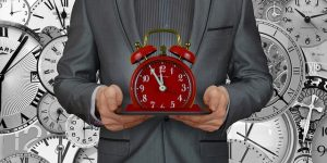 alt=red escape room timer held by corporate team building client in a suit, clocks in the background