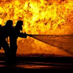 Firemen with hose fighting a large fire